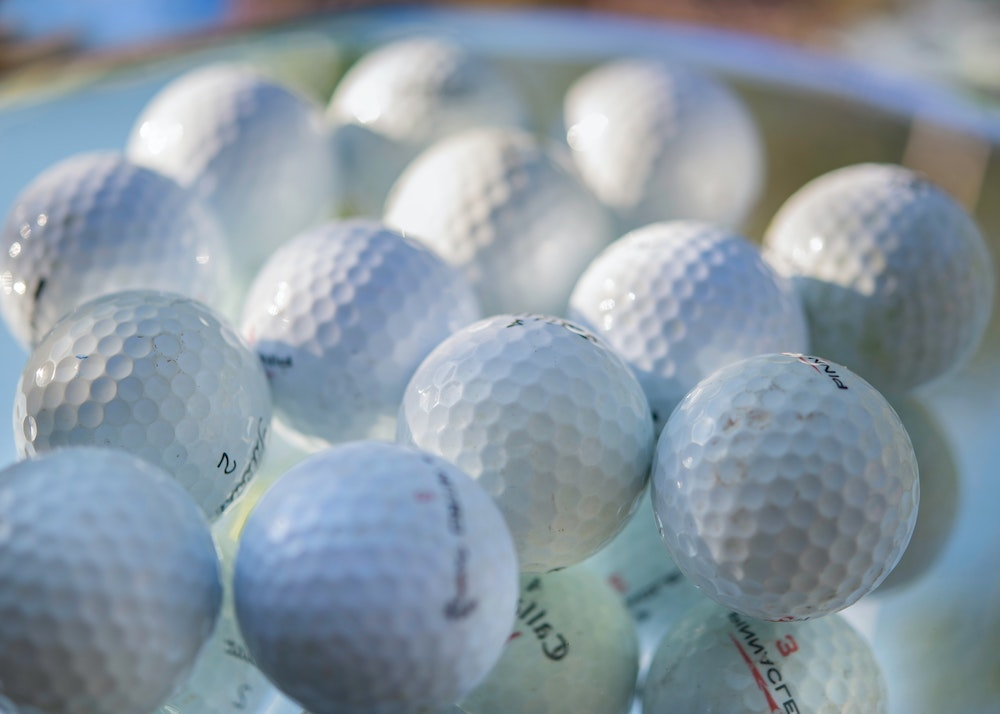 a lot of white golf balls in a pile