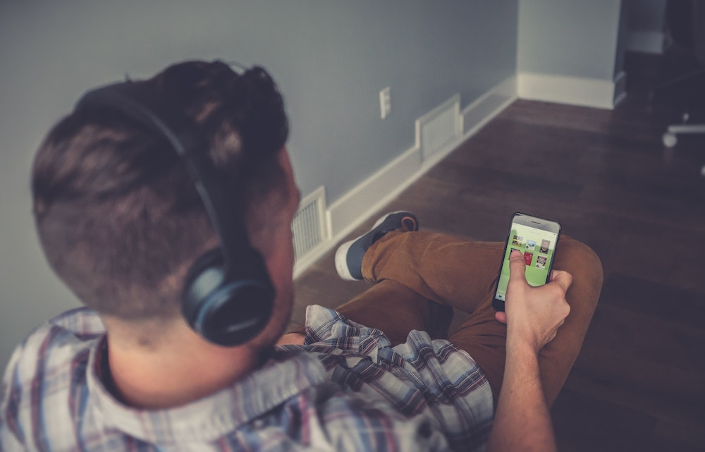 man with headphones browing phone for the best free golf audiobooks