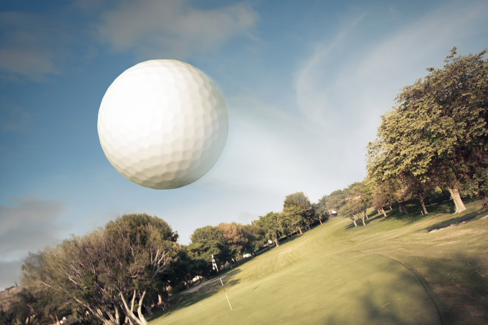 golf ball flying over a golf course with visual dimples