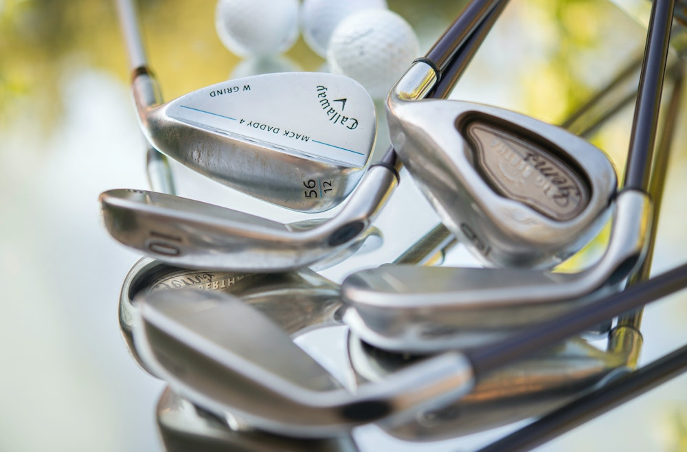 different types of golf irons laying in a pile