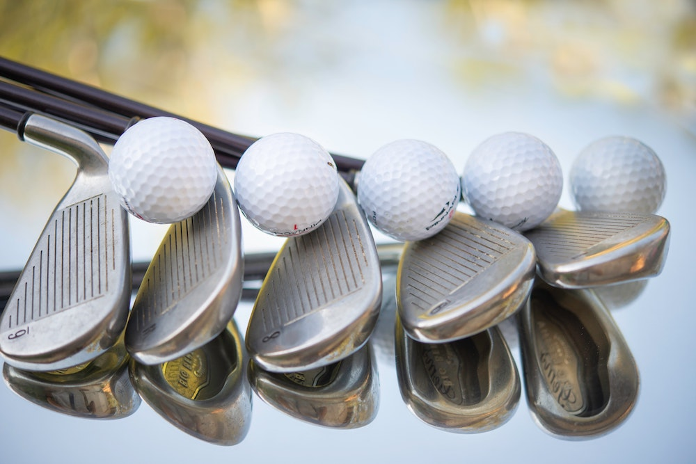 an array of the best golf irons for beginners with golf balls between